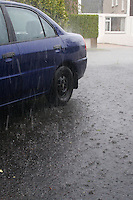 Heavy rain outside a house in Ireland blue car in the driveway