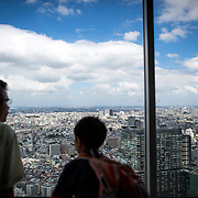 TOKYO, JAPAN - JULY 31 : A man and his son look at the Tokyo cityscape from Tokyo Observation Deck at Shinjuku, Tokyo, Japan on Sunday morning, July 31, 2016. Tokyo's more than 11 million eligible residents will decide today for a new Governor of Tokyo who will deal with improving social welfare in Japan's increasingly aging society and issues related to the hosting of the Tokyo Summer Olympics and Paralympics in 2020. (Photo: Richard Atrero de Guzman/NUR Photo)