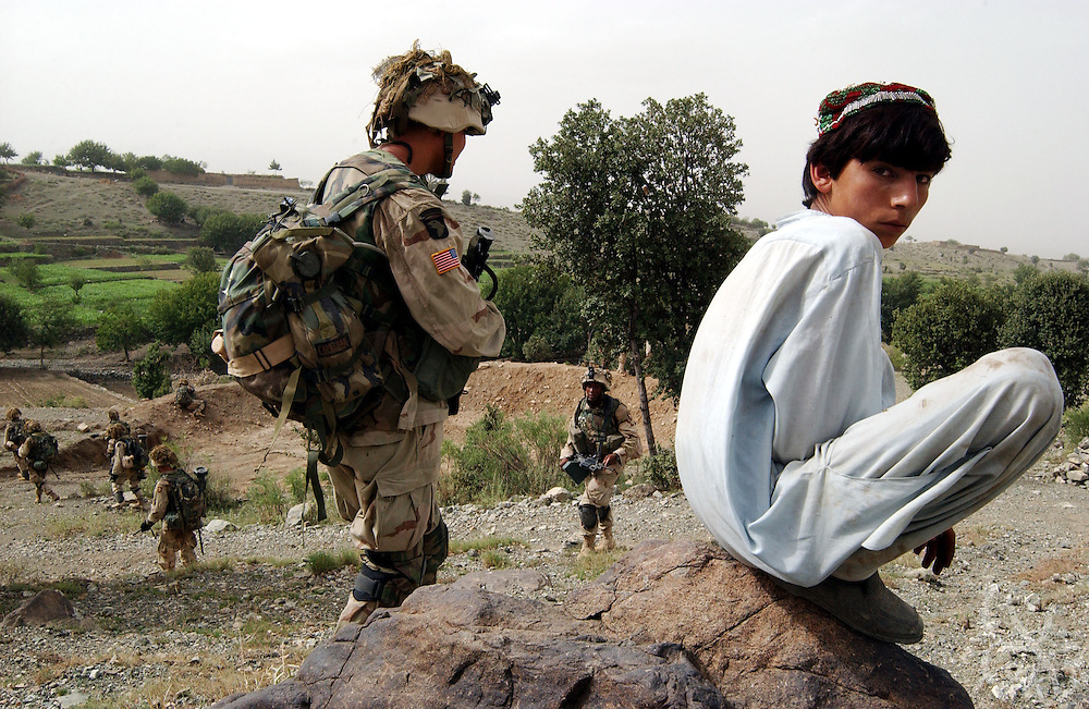"""An Afghan boy watches as US Army 101st Airborne 3-187 """"Bravo"""" company move in during a 23 July, 2002 sensitive site exploitation (SSE) mission in the town of Narizah in Southeastern Afghanistan . The three day mission, intended to deny sanctuary to Al Qaida and Taliban fighters in villages along the Pakistan-Afghanistan border resulted in the recovery of several weapons caches and one Afghan detained for questioning."""