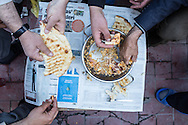 A group of men have a breakfast of sucklu yumurta (eggs fried with spicy beef sausage). Van, Turkey