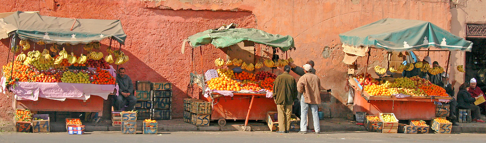 North Africa, Africa, Morocco, Marrakesh. Colorful fruit stands line a wall of Marrakesh.