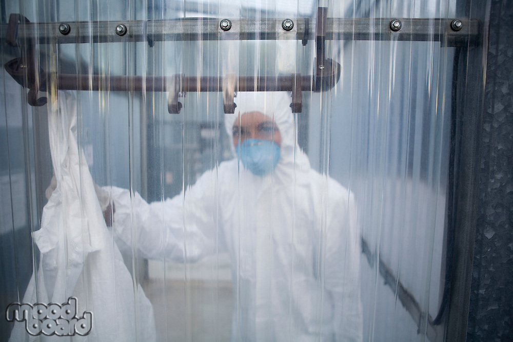 Worker in protective mask and suit behind plastic wall