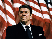 Ronald Wilson Reagan (1911-2004) 40th President of the United States (1981–1989) and 33rd Governor of California (1967–1975). Head-and-shoulders portrait with stars-and-stripes in background. American Actor Politician Republican
