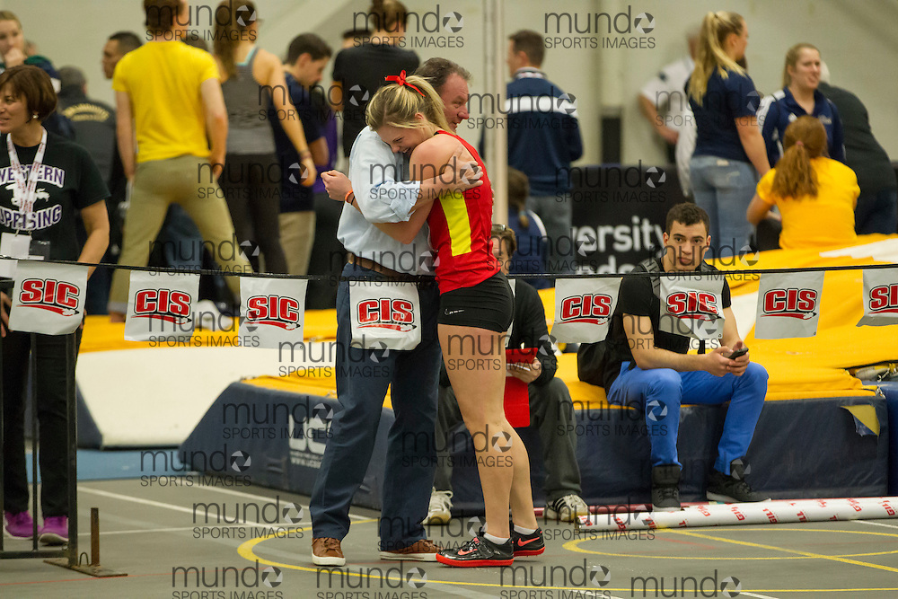 Windsor, Ontario ---2015-03-12--- Niki Oudenaarden of Calgary  gets a hug from her coach during the pentathlon high jump at the 2015 CIS Track and Field Championships in Windsor, Ontario, March 12, 2015.<br /> GEOFF ROBINS/ Mundo Sport Images