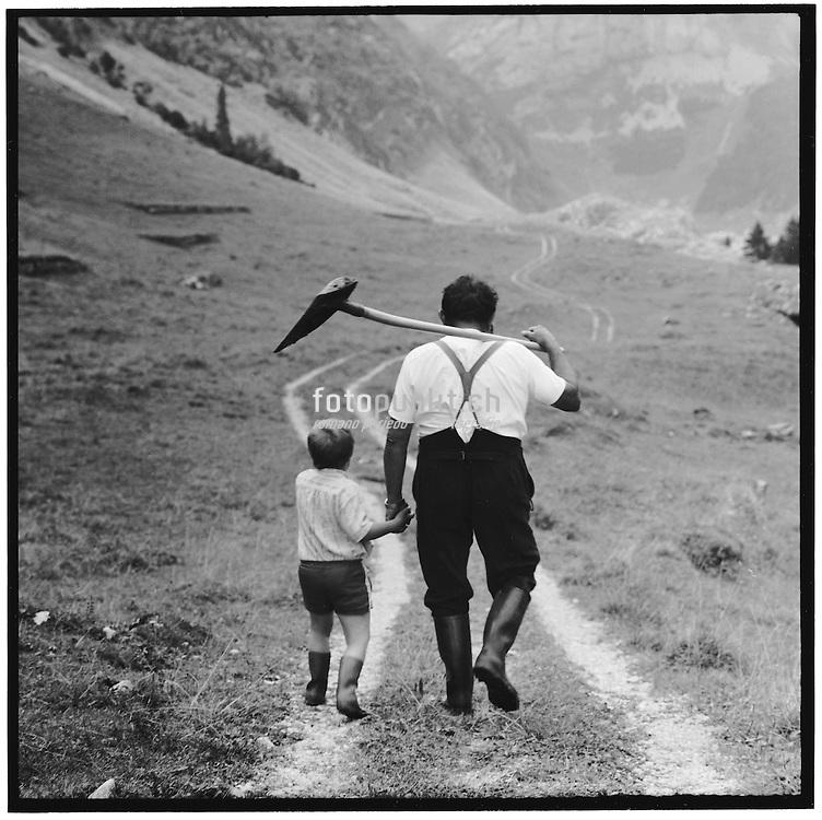 Father and son walking hand in hand on a path in the mountains, Vater und Sohn laufen Hand in Hand auf einem Weg in den Bergen, père et fils marchent main dans la main sur un chemin en montagne. © Romano P. Riedo
