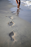 Steps of a Young woman walking in Es Cavallet beach, Ibiza
