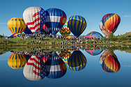 Hot air balloons are relected in Bald Eagle Lake, Steamboat Springs, Colorado, during the annual Hot Air Balloon Rodeo.