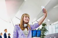 Young attractive teenage girl taking selfie in airport