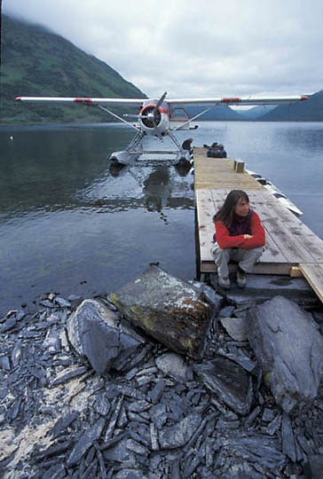 Alaska, Woman sits on dock near float plane on Kodiak Wildlife  Refuge.