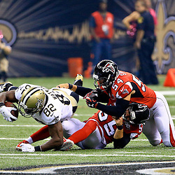 Oct 15, 2015; New Orleans, LA, USA; New Orleans Saints tight end Benjamin Watson (82) drives forward as Atlanta Falcons middle linebacker Paul Worrilow (55) and outside linebacker Nate Stupar (54) tackle during the first quarter of a game at the Mercedes-Benz Superdome. The Saints defeated the Falcons 31-21. Mandatory Credit: Derick E. Hingle-USA TODAY Sports