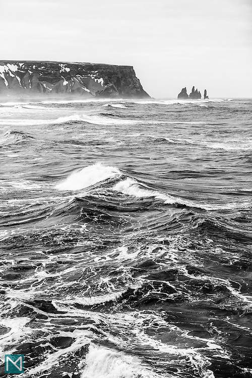 A rough sea surrounds the Reynisdrangar sea stacks at mainland Iceland's southernmost point on Reynisfjara beach