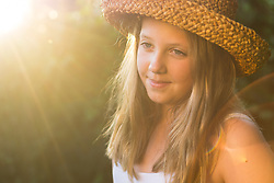 Girl in a straw hat, sunset portrait