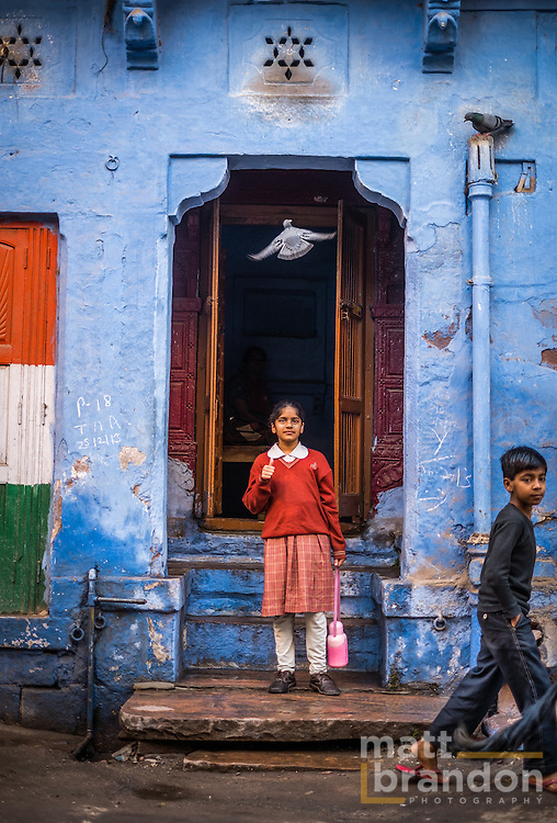 A girl leaves her home to go to school while a pigeon soars overhead. Jodhpur, Rajasthan, India
