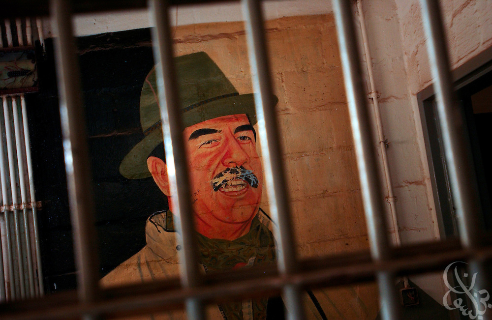 A portrait of former Iraqi leader Saddam Hussein is seen behind the bars of an office within the former Abu Ghraib prison, 20 miles west of Baghdad, Iraq August 04, 2003.  The infamous prison was renovated, renamed the Central Baghdad Detention Facility, and used to house up to several thousand Iraqis until a scandal involving abuse of prisoners by American guards forced it's closure in 2004.