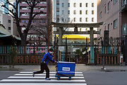 A deliveryman working for Sagawa Deliver company runs past a torii gate  at the entrance to a small shrine in Akihabara, Tokyo, Japan. Friday January 10th 2020