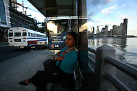 A woman waits for a bus in Panama City, Panama on Thursday, September 6, 2007. (Photo/Scott Dalton).