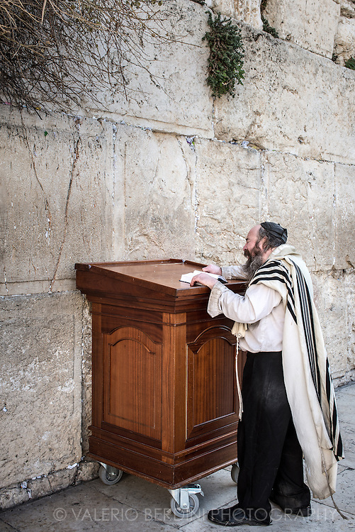 "A man in Tallit with visible tzitzit prays out loud at the Kotel in Jerusalem old city. Tzitzit is the name for specially knotted ritual fringes and are attached to the four corners of the tallit, as the Torah says ""You shall make yourself twisted threads, on the four corners of your garment with which you cover yourself"".  While for man is natural to wear a shawls and pray out loud at the Western Wall, women can be arrested for doing so. Under Israeli law women are permitted to pray at the Western Wall, but only in silence. Ultra-Orthodox Jewish men say that women should not pray out loud in public because their voices are provocative. The activist group ""Women of the Wall' is engaged since 1988 in a campaign to win the right to perform the same rituals as men at Judaism's most religious site."