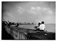 Young couple enjoys monsoon winds off of the Arabian Sea as luxury high rises pop up among art deco colonial era apartments on Marine Lind, Mumbai, India.