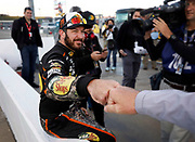 Martin Truex Jr. is congratulated after winning the pole for the NASCAR Monster Cup auto race at Kansas Speedway in Kansas City, Kan., Friday, Oct 20, 2017. (AP Photo/Colin E. Braley)