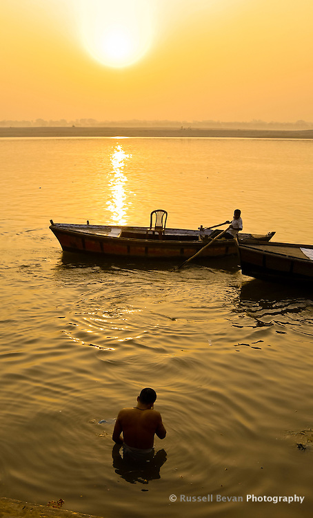 A man takes a morning bath in the River Ganges in Varanasi, Uttar Pradesh, India