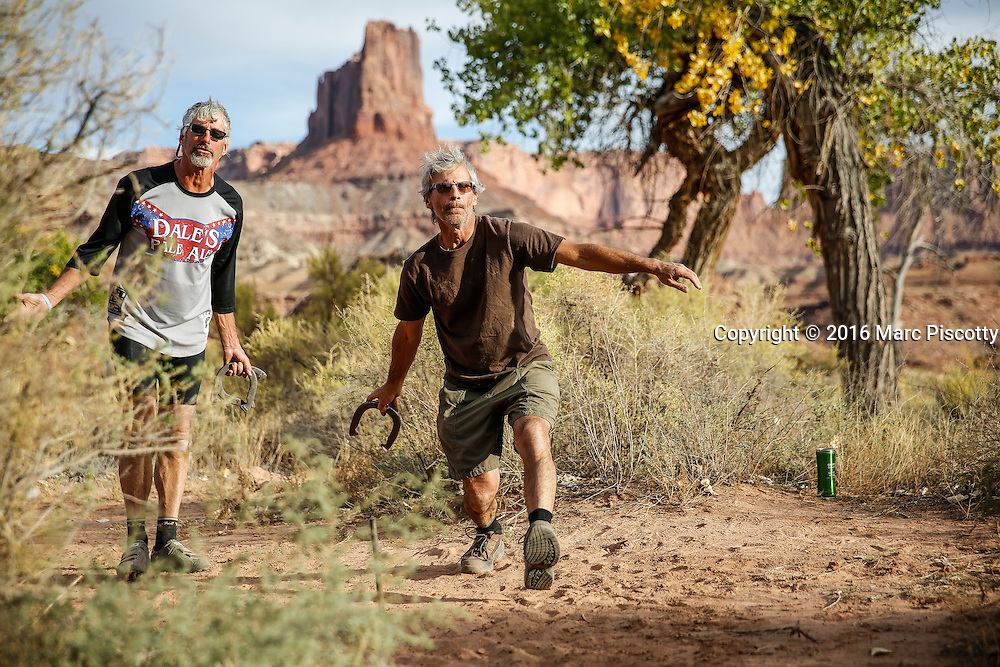 SHOT 10/14/16 5:02:22 PM - Tossing horseshoes on the White Rim trip. The White Rim is a mountain biking trip in Canyonlands National Park just outside of Moab, Utah. The White Rim Road is a 71.2-mile-long unpaved four-wheel drive road that traverses the top of the White Rim Sandstone formation below the Island in the Sky mesa of Canyonlands National Park in southern Utah in the United States. The road was constructed in the 1950s by the Atomic Energy Commission to provide access for individual prospectors intent on mining uranium deposits for use in nuclear weapons production during the Cold War. Four-wheel drive vehicles and mountain bikes are the most common modes of transport though horseback riding and hiking are also permitted.<br /> (Photo by Marc Piscotty / &copy; 2016)