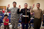 Three active duty military service members, from left, Won Choi, of South Korea, with daughter, Elizabeth, 5,  Anatoliy Pisarenko, of Russia, and Carlos Ocampo, of Columbia, take the Oath of Allegiance to become American Citizenship during the Orange County Veterans Day Program Celebration and Naturalization Ceremony at the Orange County Social Services Center in Hillsborough, North Carolina.