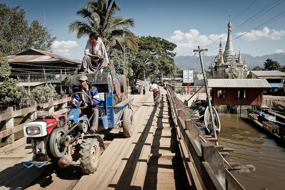 Farmers cross a bridge over the lake inle.
