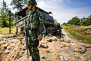 11 JULY 2013 - RAMAN, YALA, THAILAND: A Thai soldier at the scene of an IED attack against members of his unit. Eight soldiers were injured when the IED exploded under a Thai Army truck carrying soldiers back to their camp after they finished a teacher protection mision. The army routinely dispatches soldiers to protect teachers and Buddhist monks, who have been targeted by Muslim insurgents as representatives of the Bangkok government. More than 5,000 people have been killed and over 9,000 hurt in more than 11,000 incidents in Thailand's three southernmost provinces and four districts of Songkhla since the insurgent violence erupted in January 2004, according to Deep South Watch, an independent research organization that monitors violence in Thailand's deep south region that borders Malaysia.    PHOTO BY JACK KURTZ