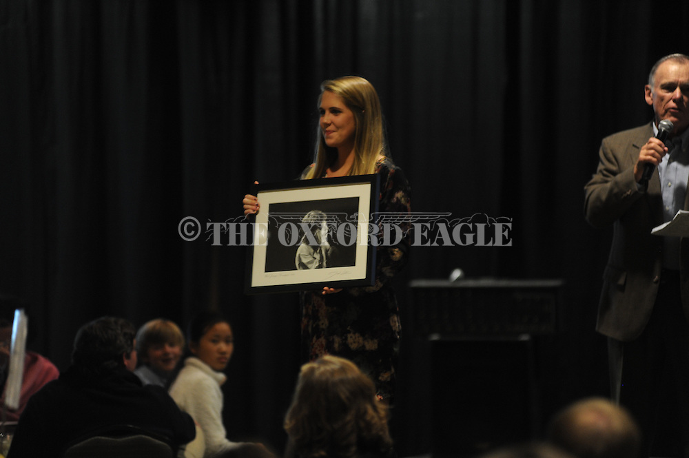 Katie Bebee displays a print of Mick Jagger up for auction during the annual Paws for Art fundraiser for the Oxford-Lafayette Humane Society, at the Oxford Conference Center in Oxford, Miss. on Thursday, November 7, 2013.