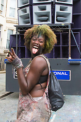 London, August 30th 2015. A woman pulls a face for the camera as she dances behind a sound system truck as it performs a sound check as revellers await the start of the Notting Hill Carnival.