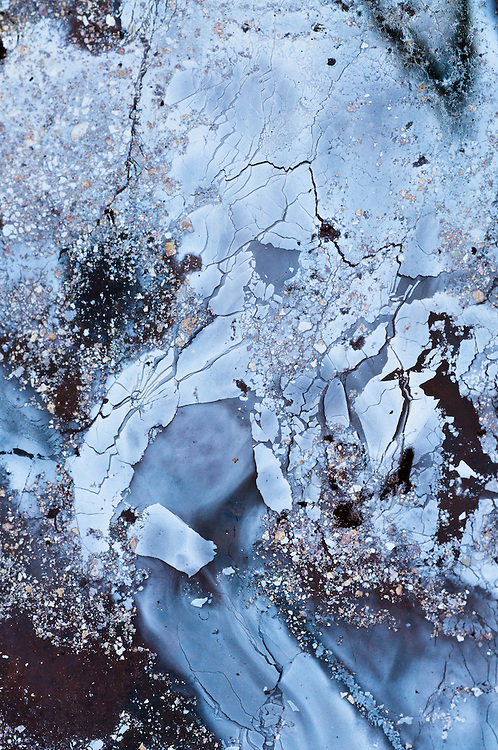 Macro photography of small puddle of water in a trail adjacent to a beaver pond in the Adirondacks. Colors and shapes come from a combination of oily film on the surface of the water, trees and clouds reflecting in the puddle and the ground at the bottom of the puddle