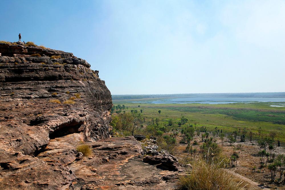 Ubirr Rock, Kakadu National Park <br /> Mas em alguns podemos, como na Rocha de Nourlangie, e na de Ubirr. Este &uacute;ltimo lugar foi o que mais mexeu comigo ao subir o enorme penedo que serve de miradouro sobre as plan&iacute;cies alagadas. &Agrave; medida que subia parecia que caminhava para a proa de um navio at&eacute; que era s&oacute; eu e o verde at&eacute; ao fim do horizonte, e atr&aacute;s, as colunas de fumo das queimadas contribu&iacute;am para a minha pequenez. &ldquo;O mundo &eacute; grandioso&rdquo; devo ter pensado.