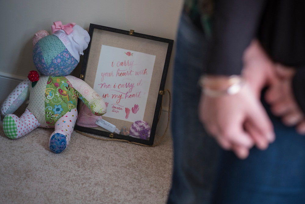 "Fredericksburg, VA  - Lindsey and Matt Paradiso, photographed inside their home, March 12, 2017 in downtown Fredericksburg, Virginia.  Lindsey, 28 years old, and Matt, 31 years old, talk about their pregnancy and subsequent ""late term abortion"" due to medical complications. Omara Rose, the name the chose for their daughter, was aborted at 25 weeks, February 26, 2016. A shadow box of memories of their daughter including their daughters hand and foot prints sits with teddy bear while the couple holds hands. Photo Justin Ide"