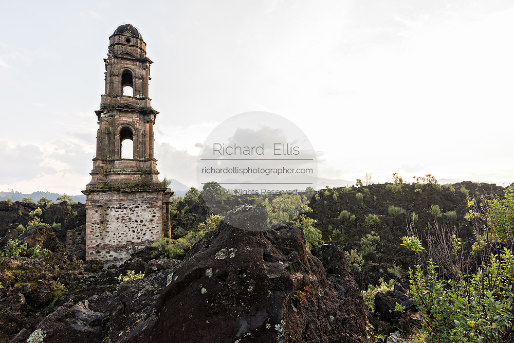 The steeple of San Juan Parangaricutiro church poking up out of a sea of dried lava rock at sunset in the remote village of San Juan Parangaricutiro, Michoacan, Mexico. This church is the only remaining structure left buried in the eight-year eruption of the Paricutin volcano which consumed two villages in 1943 and covered the region in lava and ash.