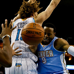 Mar 25, 2013; New Orleans, LA, USA; Denver Nuggets shooting guard Andre Iguodala (9) passes as New Orleans Hornets center Robin Lopez (15) defends during the second half of a game at the New Orleans Arena. The Hornets defeated the Nuggets 110-86. Mandatory Credit: Derick E. Hingle-USA TODAY Sports