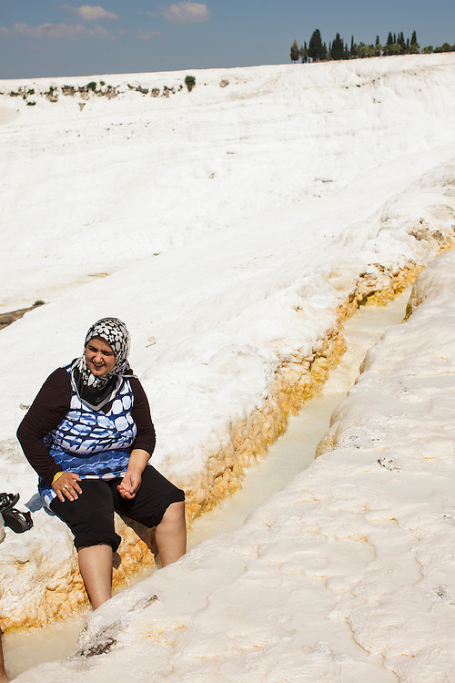 A tourist wet her feet on the water that runs on the floor at Pamukkale. The hard, white mineral deposits, which from a distance resemble snow, are caused by the high mineral content of the natural spring water which runs down the cliff and congregates in warm pools on the terraces. This is such a popular tourist attraction that strict rules had to be established in order to preserve its beauty, which include the fact that visitors may no longer walk on the terraces. Those who want to enjoy the thermal waters, however, can take a dip in the nearby pool, littered with fragments of marble pillars.