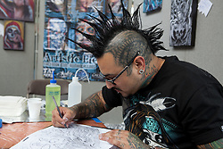 © Licensed to London News Pictures. 28/09/2012. London, UK. A tattoo artist sketches new designs. The 8th London Tattoo convention opened today, 28 September 2012 at Tobacco Dock in East London. The convention attracts tattoo artists and body art fans from all over the world and runs until 30 September 2012. Photo credit : Vickie Flores/LNP.