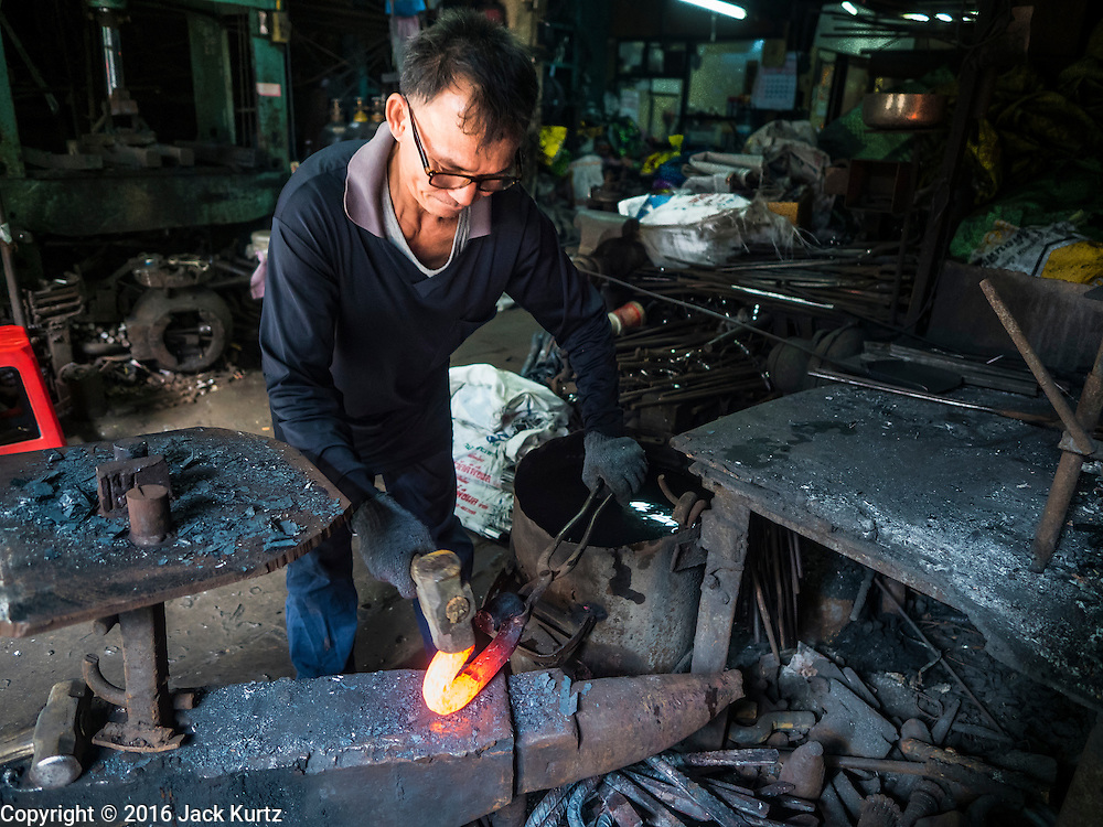25 JANUARY 2016 - BANGKOK, THAILAND: The operator of a small one person workshop that makes heavy chains for boat anchors hammers the still glowing links into shape. The metal for the chains is heated until it glows red and then it's pounded into shape. The Talat Noi neighborhood in Bangkok started as a blacksmith's quarter. As cars and buses replaced horse and buggy, the blacksmiths became mechanics and now the area is lined with car mechanics' and blacksmiths' shops.         PHOTO BY JACK KURTZ