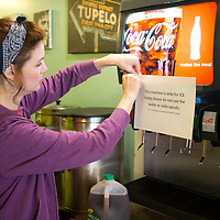 Amanda Hayden, co-owner of Cafe 212, hangs a sign instructing customers to not use the water or soda spouts  because of the boil water notice in effect for Tupelo Water and Light customers Friday morning at the restaurant.