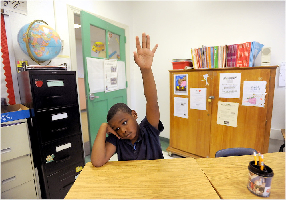 Tavion Jenkins raises his hand to answer a question during his reading class.