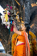 KADIRI, INDIA - 03rd November 2019 - Hindu woman ties ribbon to Hindu shrine for fetility blessing at Kadiri temple, Andhra Pradesh, South India.