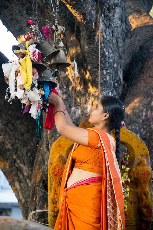 KADIRI, INDIA - 03rd November 2019 - Hindu woman ties ribbon to Hindu shrine for fetility blessing at Kadiri temple, Andhra Pradesh, South India.