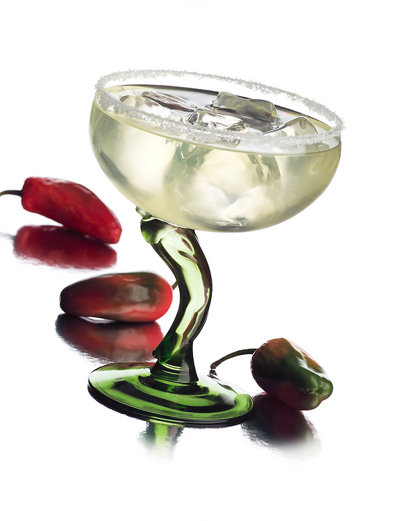 A margarita in a glass with a pepper stem