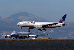 Boeing 777-222 (N771UA) operated by United Airlines landing past Boeing 747-409(F) (B-18718) operated by China Airlines for China Airlines Cargo, San Francisco International Airport (KSFO), San Francisco, California, United States of America