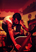 Tattooed man standing against and playing a double bass, Brazil, 2000's