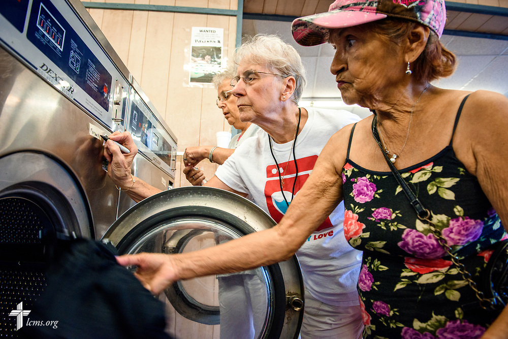 "As Margaret Mann loads her laundry into the washing machine, volunteers Joyce Bauer and Elma Richmond (rear) from St. Paul Lutheran Church, San Antonio, Texas, assist during the  Laundry Love event on Wednesday, Aug. 2, 2017, at the E-Z Wash laundromat in San Antonio. The monthly ministry event is supported by a grant through the ""Stand With Your Community"" program, which was made possible by a partnership between the LCMS, Thrivent Financial and Lutheran Church Extension Fund. LCMS Communications/Erik M. Lunsford"