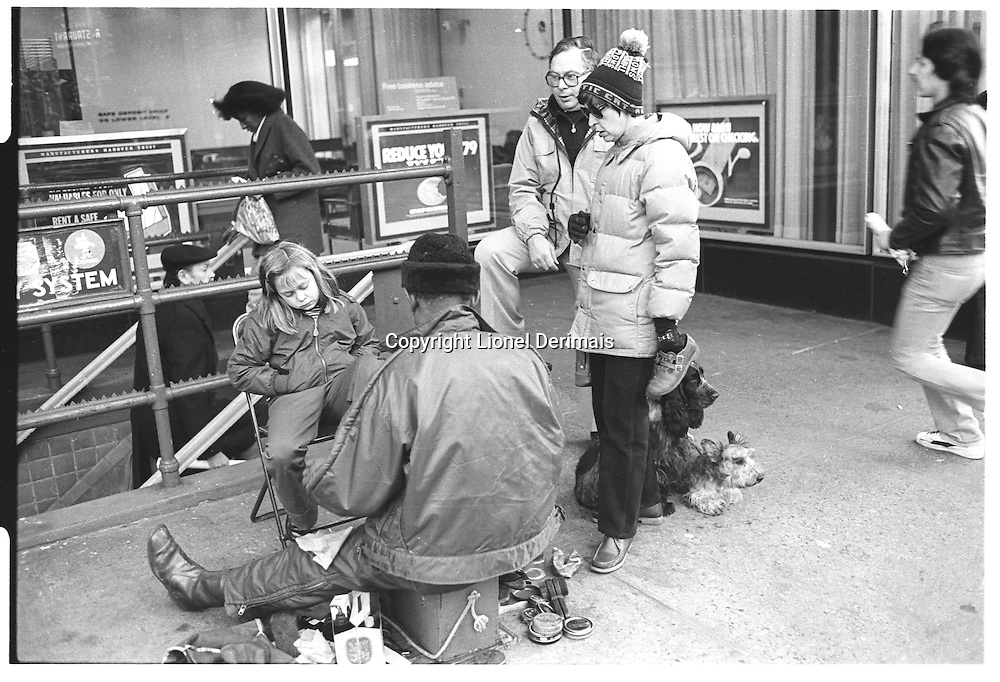 Girl looking bored getting her shoes polished with her parents and dogs by her sideStreet photography. 1980