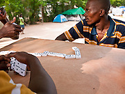 16 NOVEMBER 2010 - PORT-AU-PRINCE: HAITI: Haitian men play dominoes in a tent city in a park in the Delmas neighborhood of Port-au-Prince. The Jan. 12 earthquake has left hundreds of thousands of Haitians homeless and 10 months after the earthquake Haitians are still living in tents donated by foreign governments and NGOs. PHOTO BY JACK KURTZ