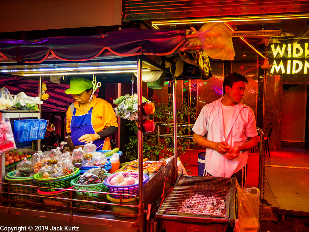 "27 FEBRUARY 2019 - BANGKOK, THAILAND: A street food stall that caters to workers on Soi Cowboy, one of Bangkok's ""adult entertainment"" districts waits for customers. Bangkok, a city of about 14 million, is famous for its raucous nightlife. But Bangkok's real nightlife is seen in its markets and street stalls, many of which are open through the night.         PHOTO BY JACK KURTZ"