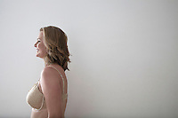 Side view of woman in bra smiling over gray background